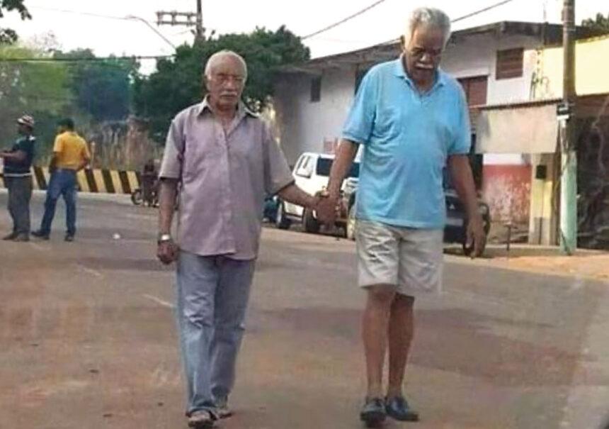 Viejo amigo lo ayuda a caminar de la mano porque no puede ver. Amistad verdadera